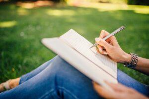 Henkilö kirjoittamassa muistivihkoon puistossa