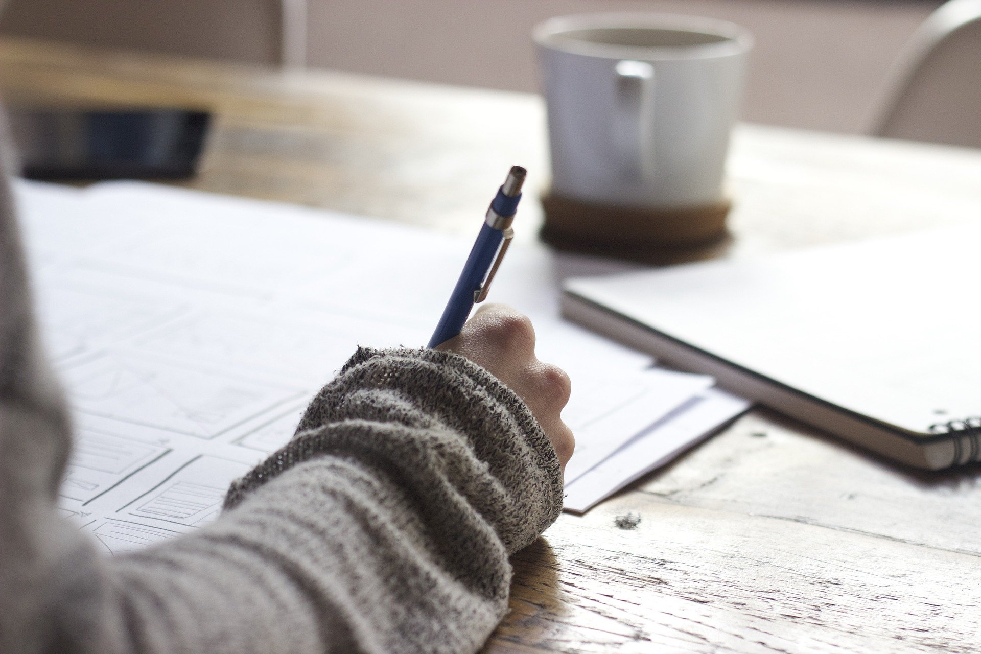 Kuvassa käsi, joka kirjoittaa paperille
