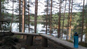 Kuva nuotiopaikalta. Taustalla mäntyjä ja peilityyni järvi.